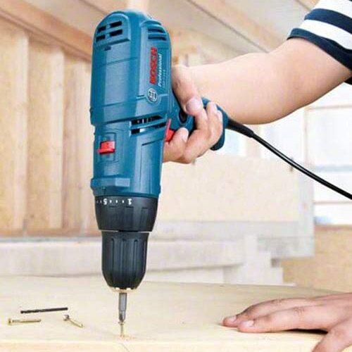 Parafusadeira elétrica Bosch apertando o parafuso em uma tábua